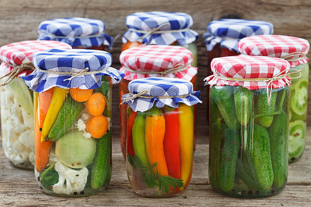 Jars of pickled vegetables Jars of pickled vegetables on wooden table. Marinated food. fermenting stock pictures, royalty-free photos & images