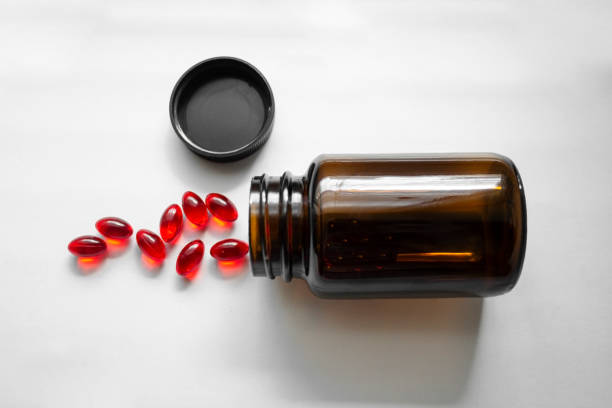 Jars of red pills. Tablets poured out of the jar on white background. Glass brown pill bottle. Jars of red pills. Tablets poured out of the jar on white background. Glass brown pill bottle. biohacking stock pictures, royalty-free photos & images