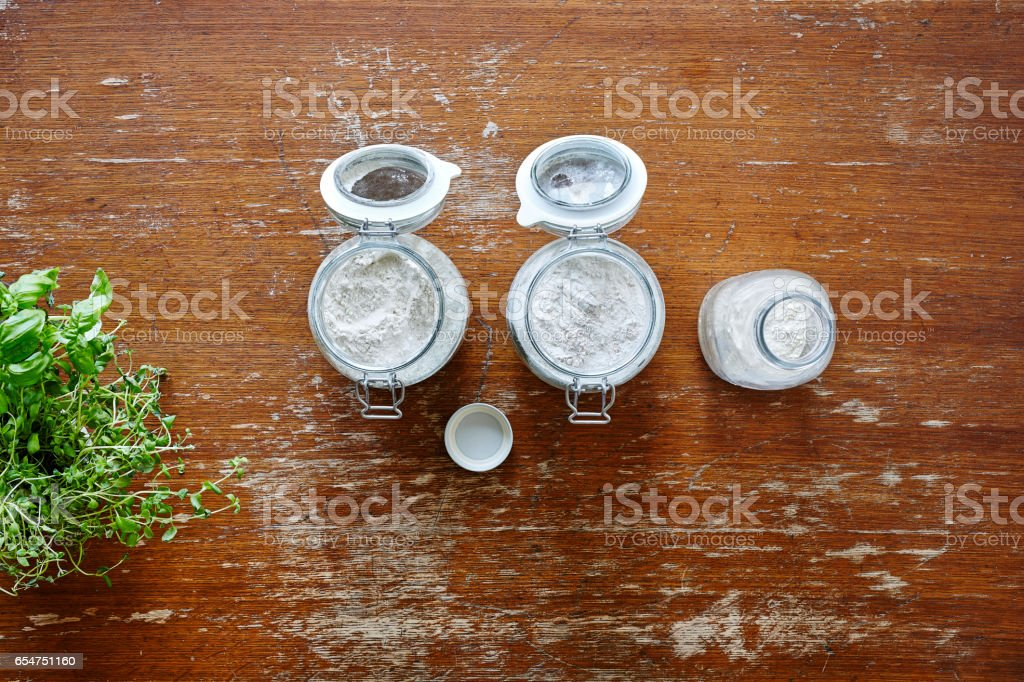 jars with flours on wooden table stock photo