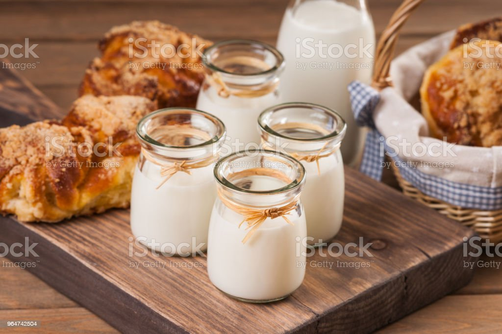 Jars with milk and bread buns on a cutting board royalty-free stock photo