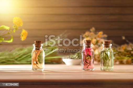 Three jars with essence of plants and plants inside on wooden table with plants and herbs and wooden background . Front view. Horizontal composition.