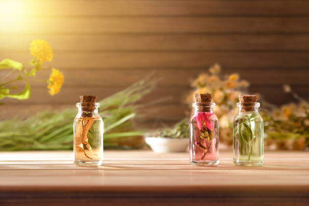 Jars with plant essence on table and wooden background front stock photo