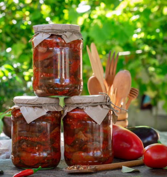 gläser mit gerollten marinierte auberginen in gemüsesauce - peperoni stiche stock-fotos und bilder