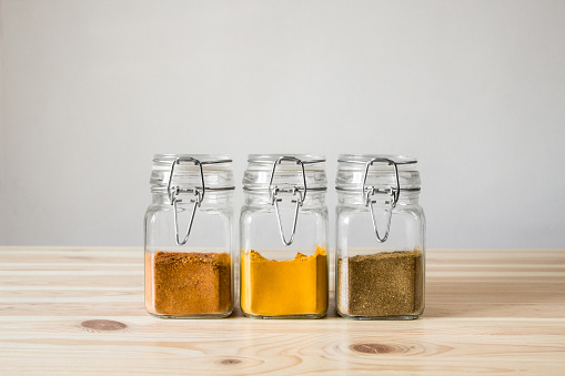 istock Jars with spices on light wood table. 600084588
