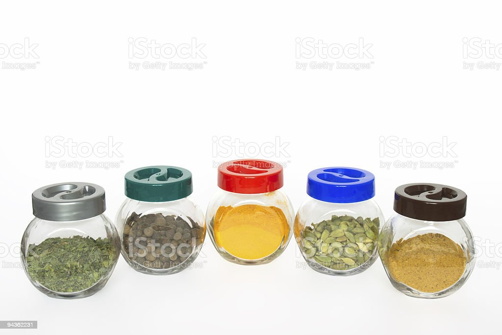 Jars with various spices (fenugreek,allspice tree, turmeric, cardamom, curry) royalty-free stock photo