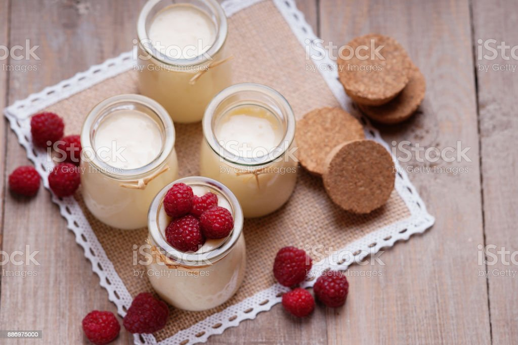 Jars with yogurt and raspberries stock photo