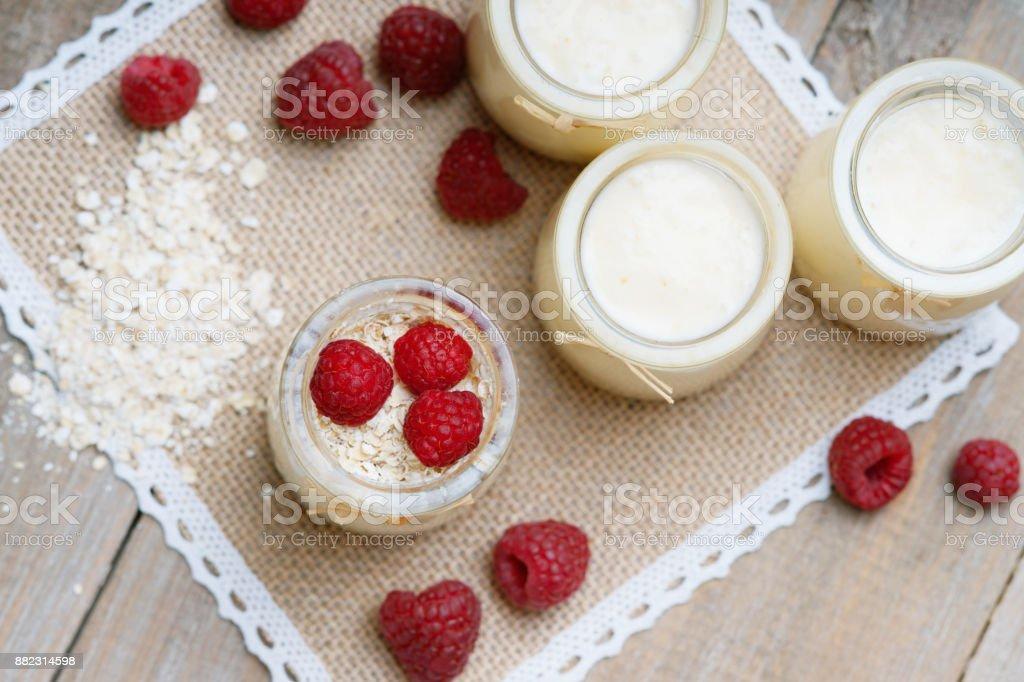 Jars with yogurt, raspberries and oat flakes stock photo