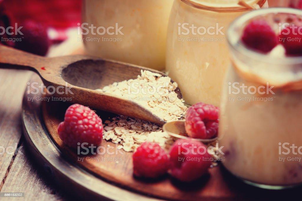Jars with yogurt, raspberries, wooden scoop and oat flakes stock photo