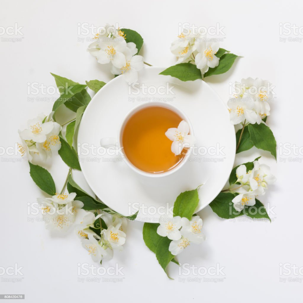 Jasmine Leaves And Flowers Around Cup Of Green Tea On White