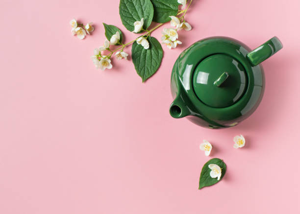 Jasmine tea with teapot, flowers and leaves on pink background Jasmine tea with teapot, flowers and leaves on pink background, copy space, top view teapot stock pictures, royalty-free photos & images