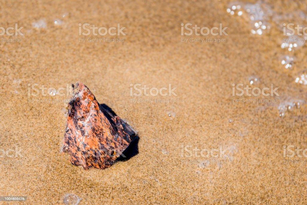 Jasper stone on a sandy beach close up