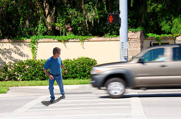 Jaywalking man about to be run over by truck stock photo