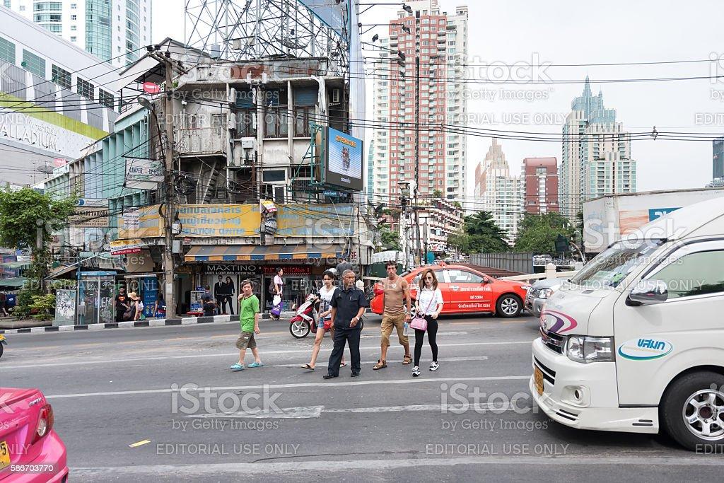 Jaywalking, Pedestrians cross a road in slow moving traffic stock photo