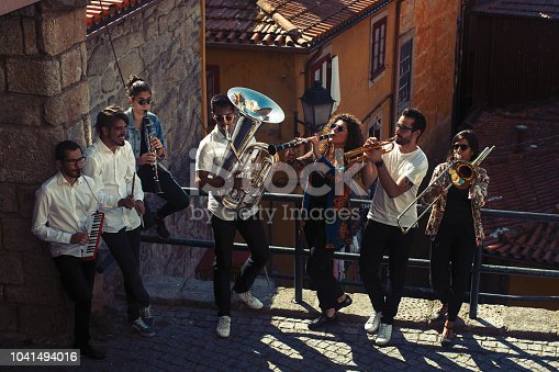 Jazz band a group of musicians with wind instruments playing on the street of the city.