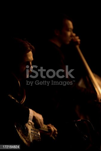 Sepia tint to a shot of a jazz guitarist and bass player playing a live gig.