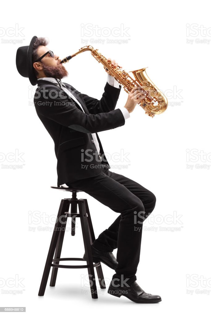 Jazz musician seated on a chair playing a saxophone stock photo