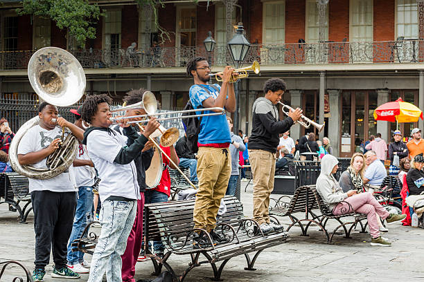 Jazz Musicians Busk in Jackson Square, New Orleans New Orleans, USA - November 8, 2015: A group of young men play jazz music as people sit in Jackson Square in the French Quarter of New Orleans, Louisiana. theasis stock pictures, royalty-free photos & images