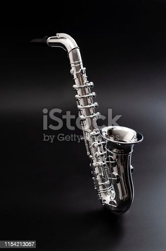 Jazz nightclub, blues music and woodwind instrument concept theme with a silver saxophone floating over a black background