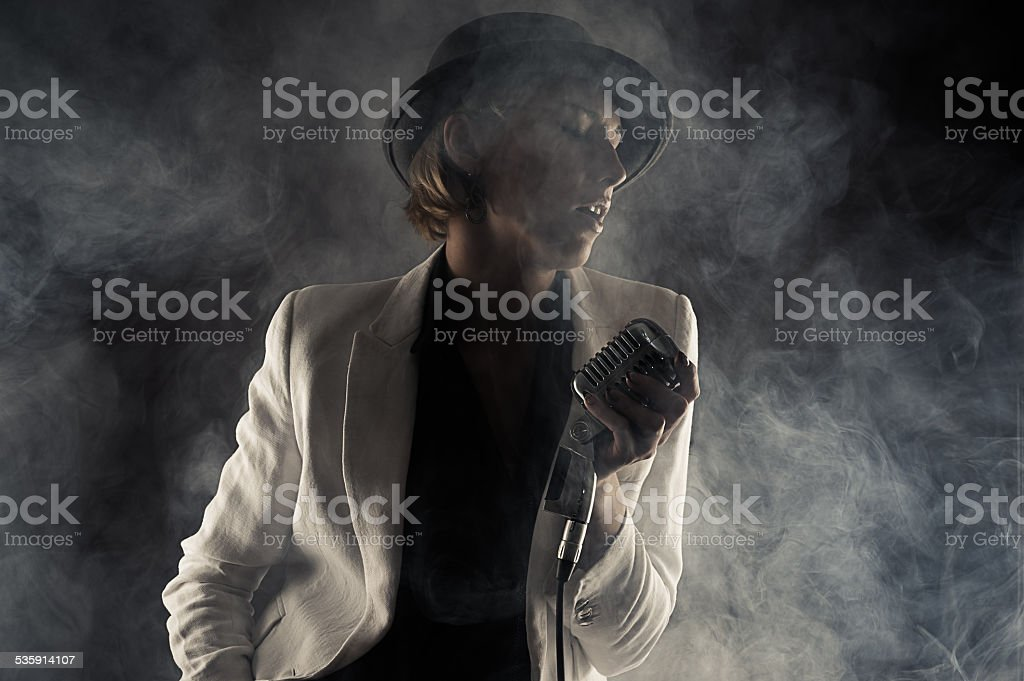 jazz singer woman with retro microphone in smoke stock photo