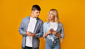 istock Jealous guy looking at girlfriend's cellphone, reading her messages 1178525760