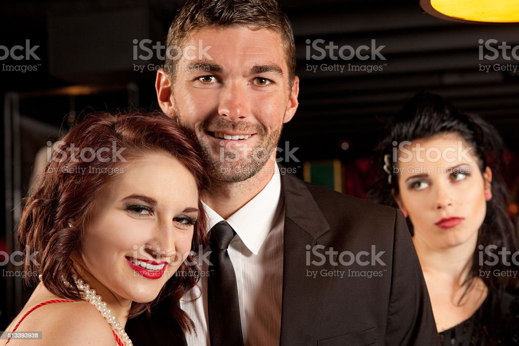 Jealous Woman In Background Of Couple's Photo stock photo