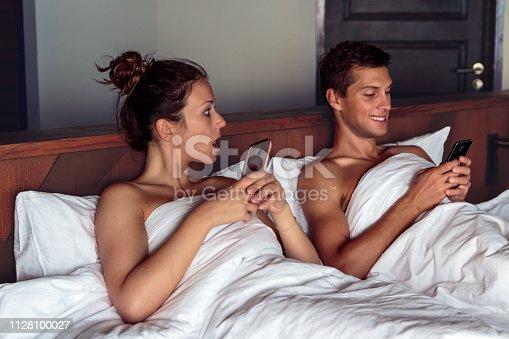 660639880 istock photo Jealous woman spying her husband mobile phone in bedroom. 1128100027