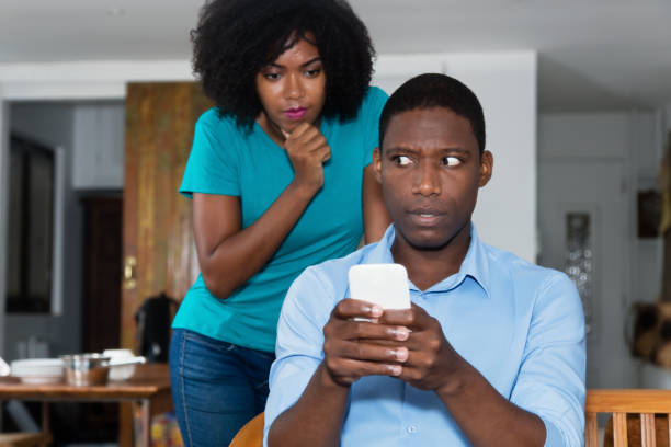 Jealousy african american woman checking chat on cellphone of boyfriend Jealousy african american woman checking chat on cellphone of boyfriend at home dishonesty stock pictures, royalty-free photos & images