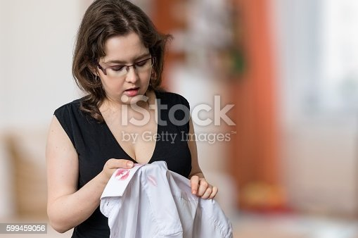 185866319istockphoto Jealousy wife found lipstick stains on white shirt of husband. 599459056