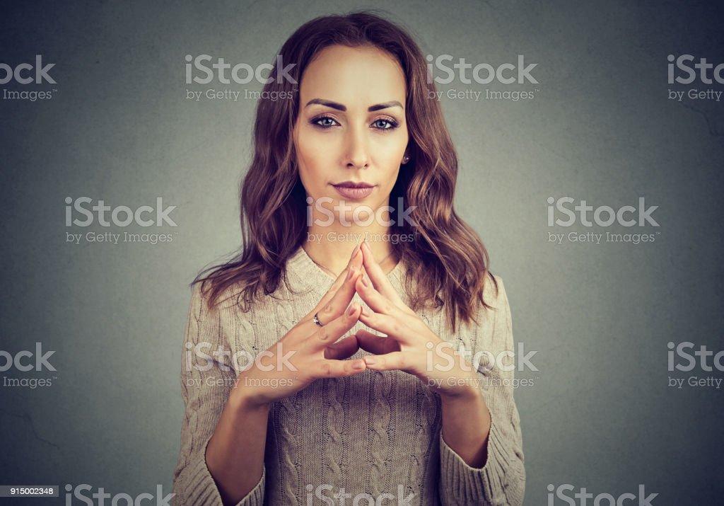 Jealousy woman plotting and posing on gray stock photo