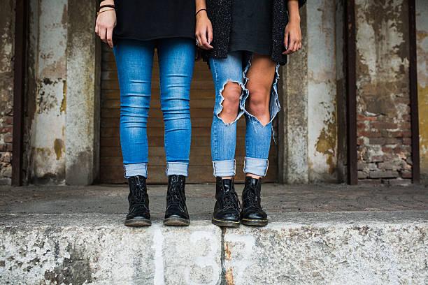 jeans und stiefeln zwei teenager - siamesische zwillinge stock-fotos und bilder