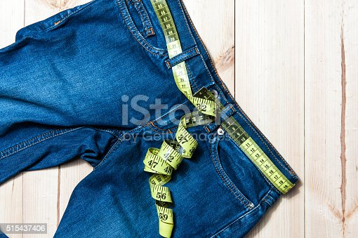 istock jeans and centimeter on a wooden background 515437406