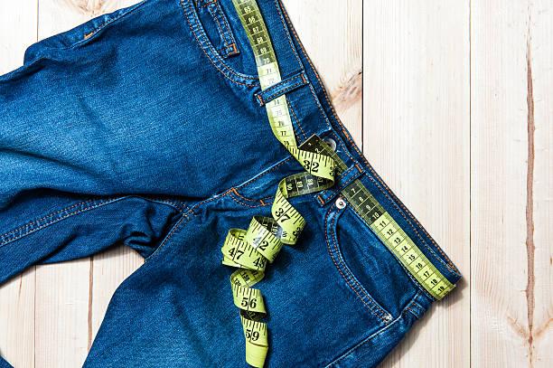 jeans und ein hölzerner hintergrund cm - damen sporthose übergröße stock-fotos und bilder