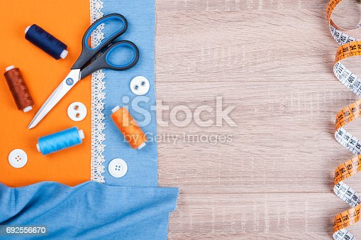 istock Jeans and cotton fabrics for sewing, lace, measuring tape and accessories for needlework on old wooden background. Spool of thread, scissors, buttons, sewing supplies. Set for needlework top view 692556670