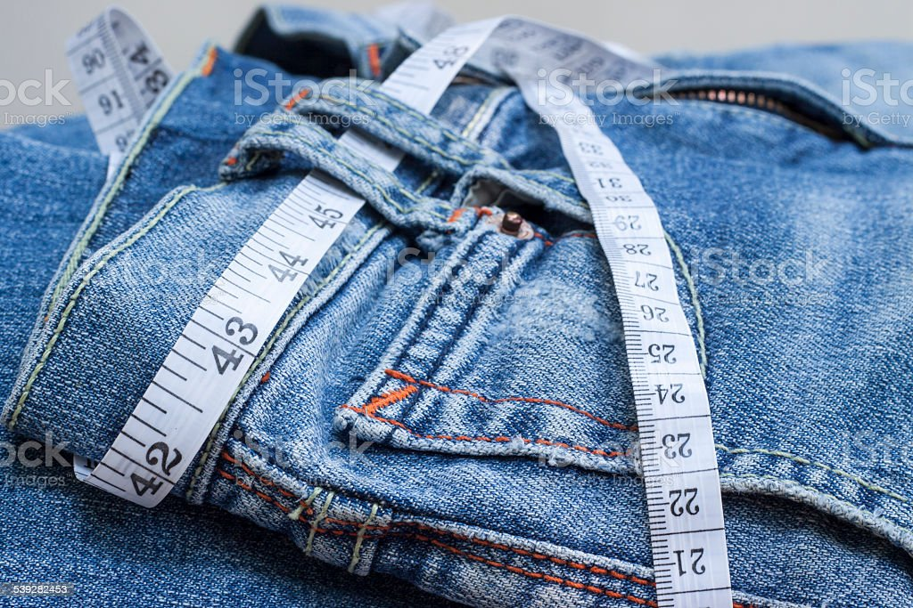 Jeans and measuring tape stock photo