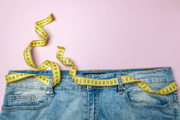 Jeans and yellow measuring tape instead of belt on pink background. Concept of weight loss, diet, detox, thin waist Jeans and yellow measuring tape instead of belt on pink background. Concept of weight loss, diet, detox, thin waist. Copy space for text dieting stock pictures, royalty-free photos & images