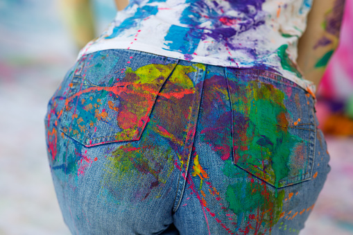 Jeans are painted with colorful paints at the festival.
