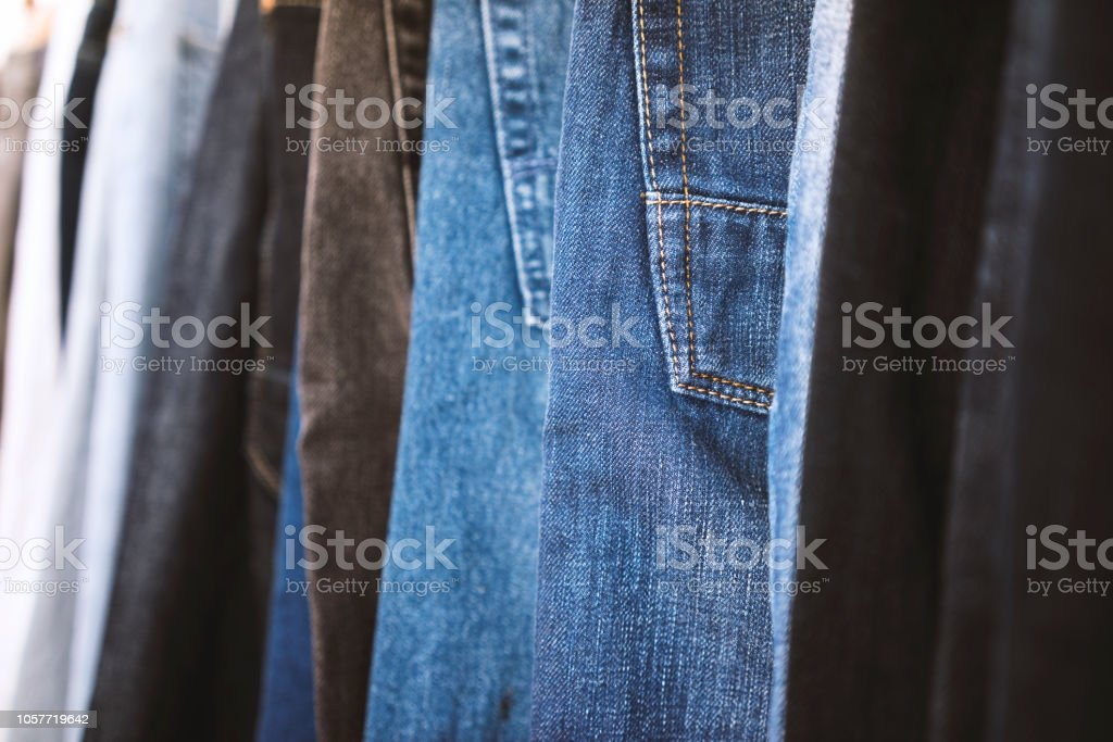 Jeans arranged in a row on cloth hanger