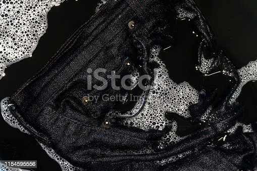 Jeans blue dark soak in sponge washing and wet in sponge water dirty black, Colored jeans clothes