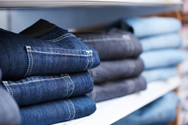 jeans clothes on shelf in shop - jeans stock photos and pictures