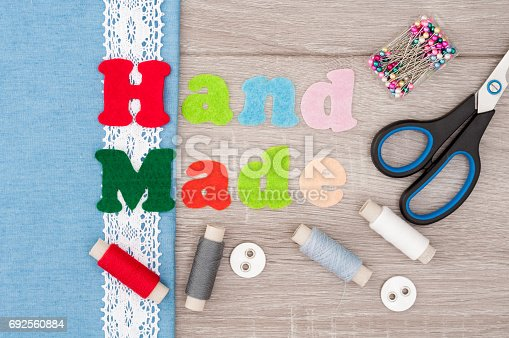istock Jeans fabric for sewing, lace, accessories for needlework and inscription Handmade of felt on old wooden background. Spool of thread, scissors, buttons, sewing supplies. Set for needlework top view 692560884