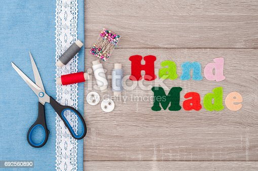istock Jeans fabric for sewing, lace, accessories for needlework and inscription Handmade of felt on old wooden background. Spool of thread, scissors, buttons, sewing supplies. Set for needlework top view 692560890