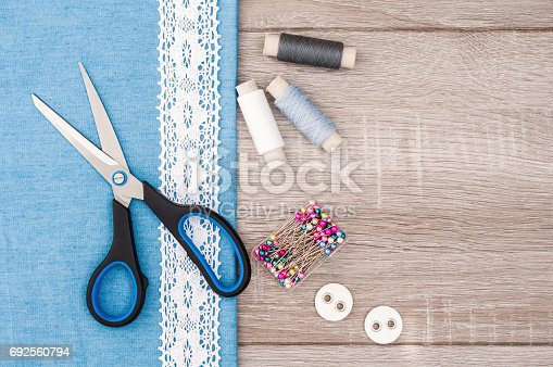 istock Jeans fabric for sewing, lace and accessories for needlework on old wooden background. Spool of thread, scissors, buttons, sewing supplies. Set for needlework top view 692560794