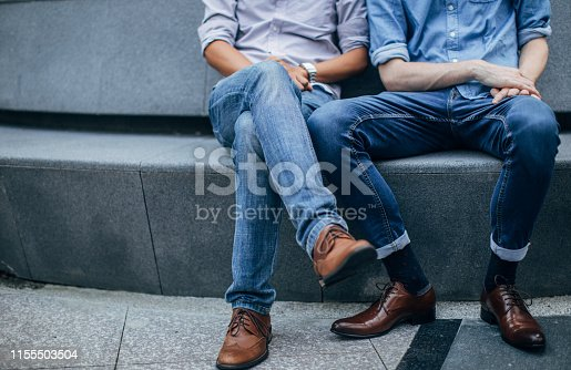 Young guy couple in jeans and brown shoes sitting on the street.