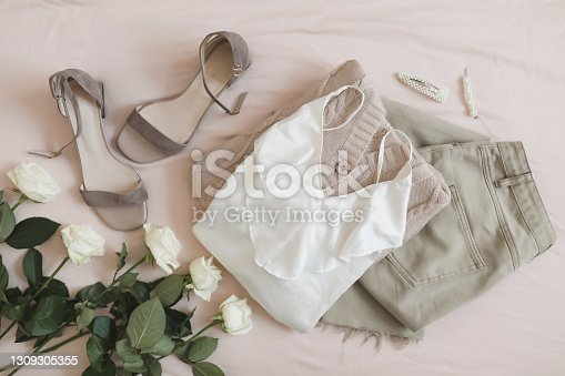 Jeans, knitted sweater, shoes and roses top view on beige background. Overhead view of woman's casual outfit. Trendy stylish women clothes. Flat lay