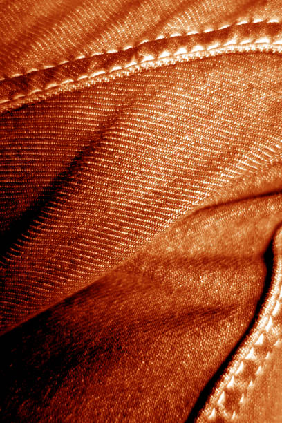 Jeans on leg close-up in orange color. stock photo