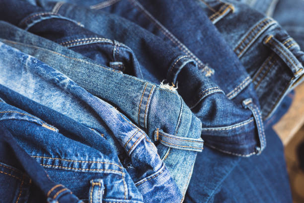 jeans scattered on a wooden background - jeans stock photos and pictures