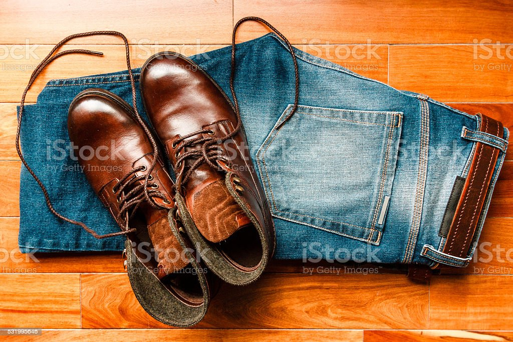 Jeans with brown leather boots over wooden floor stock photo