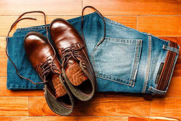 jeans mit braune leder-stiefel über holzboden - nähfuß stock-fotos und bilder