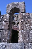 A section of the ruins of Jedburgh Abbey in Jedburgh Scotland viewed through a stone arch window.