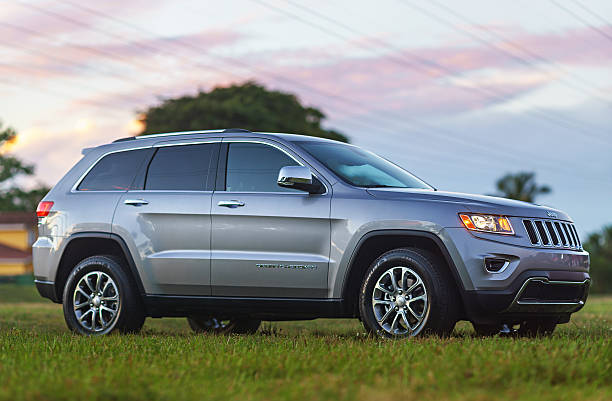 Jeep Grand Cherokee SUV 2014 Miami, USA - February 6, 2014: Metallic Silver Jeep Grand Cherokee 4x2 2014 SUV parked outside in a suburban grass field in the afternoon. 2014 stock pictures, royalty-free photos & images